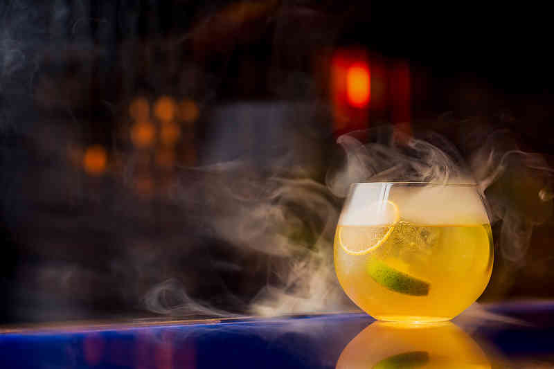 Yellow cocktail with smoke coming out of it