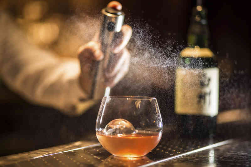 Bartender making a Smoky Negroni cocktail