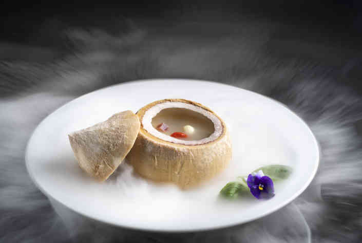 Chicken soup in coconut surrounded by smoke