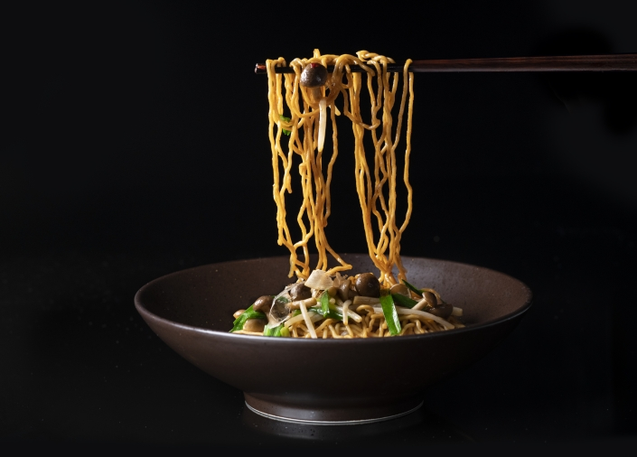 Hakka noodles being pulled up with chopsticks