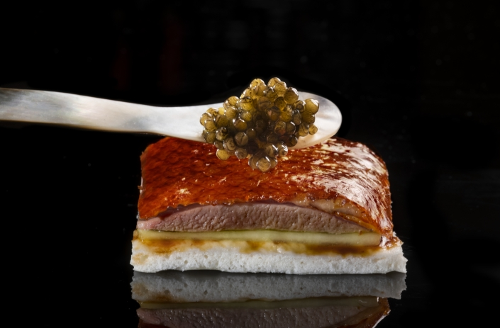 Peking duck on pancake being topped with caviar
