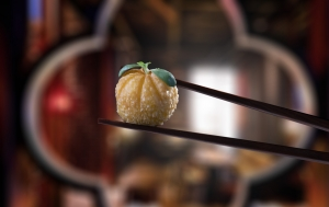 Roasted duck pumpkin puff being held by chopsticks