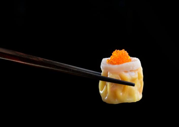 Scallop dim sum being held up by chopsticks