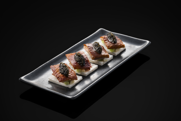 Slices of peking duck topped with caviar