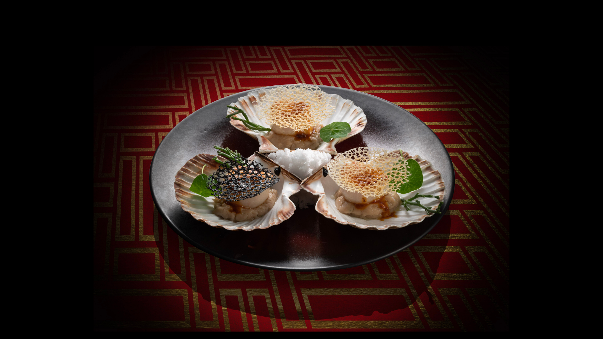 Three scallops served inside seashells on a plate