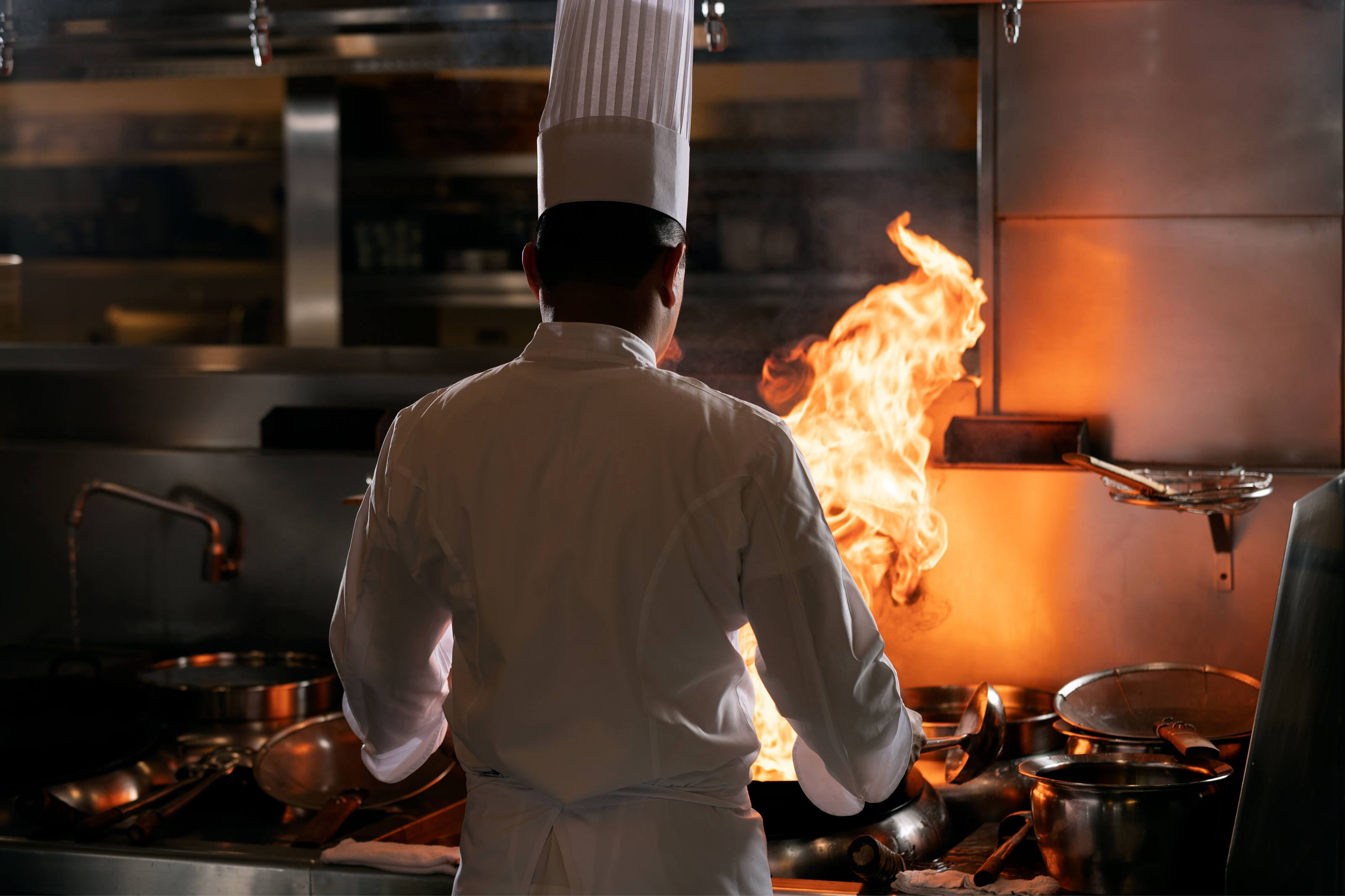 Chef standing in front of the flame of the wok